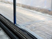The edges of an enclosure prepared to remove asbestos, polythene sealed with cloth tape